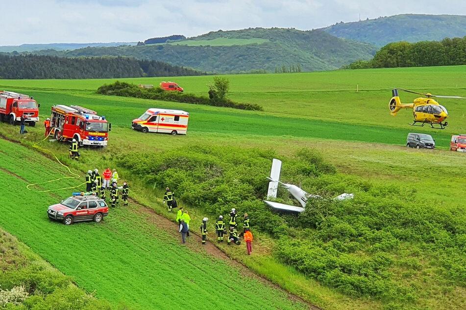 Ein Rettungshubschrauber und Rettungsfahrzeuge stehen an der Absturzstelle. Bei dem Unglück nahe Bad Sobernheim sind zwei Menschen schwer verletzt worden.