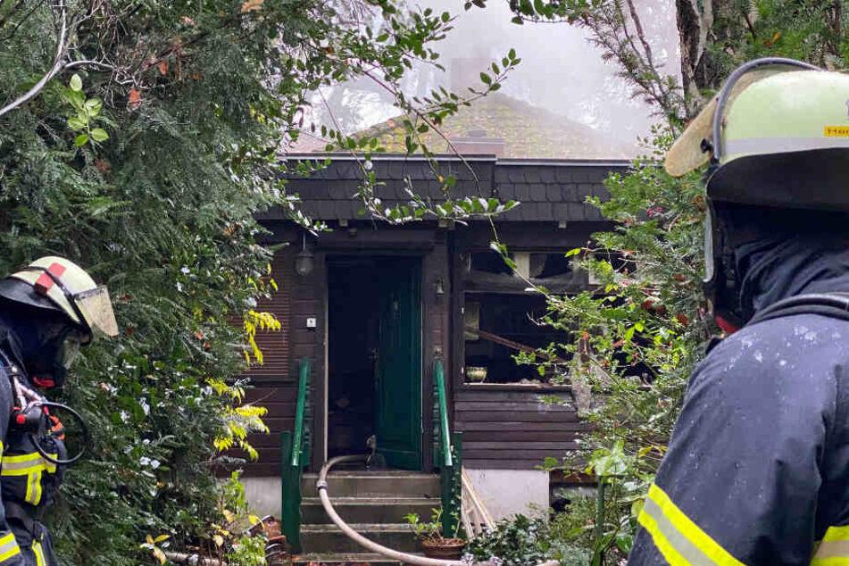 Feuerwehrkräfte stehen vor dem brennenden Haus.