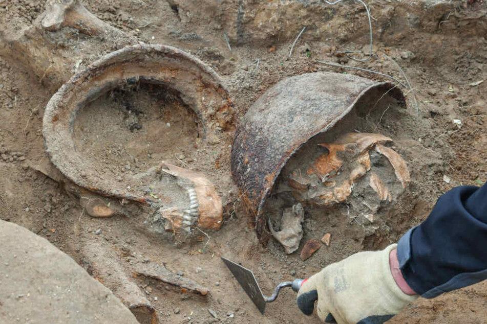Zwei Stahlhelme und die sterblichen Überreste von zwei Soldaten bei Grabungen in einem früheren Schützengraben aus dem Zweiten Weltkrieg.