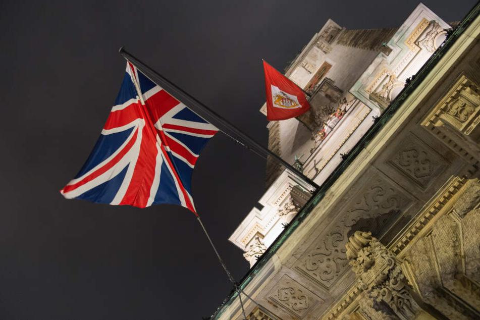 Eine britische Flagge hängt neben einee Fahne mit dem Wappen von Hamburg am Rathaus der Hansestadt.