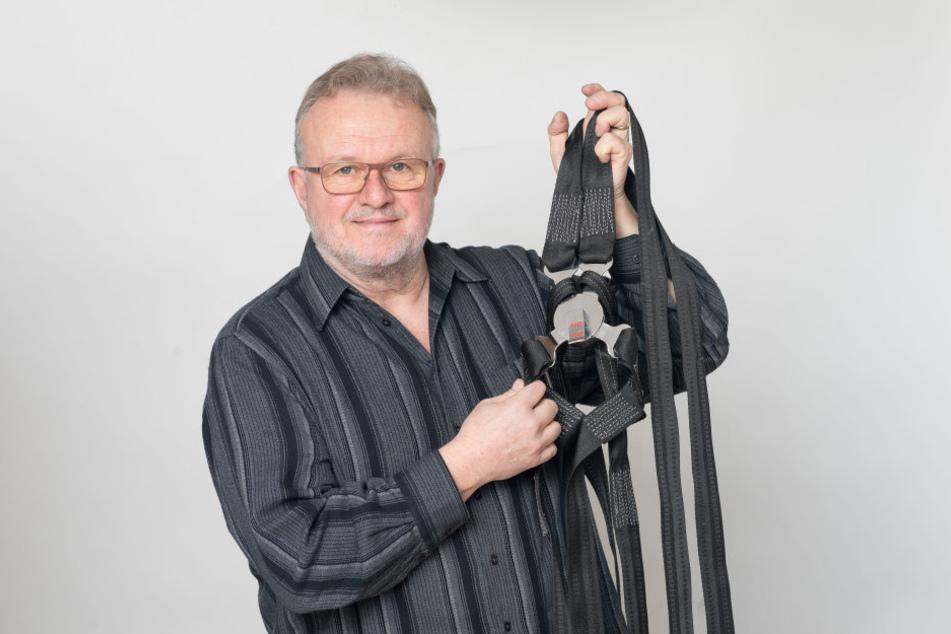 Ex-Rennfahrer Jürgen Meißner (66) in seinem Arbeitszimmer. Er hält die  Erinnerung an den Ost-Rennsport hoch.