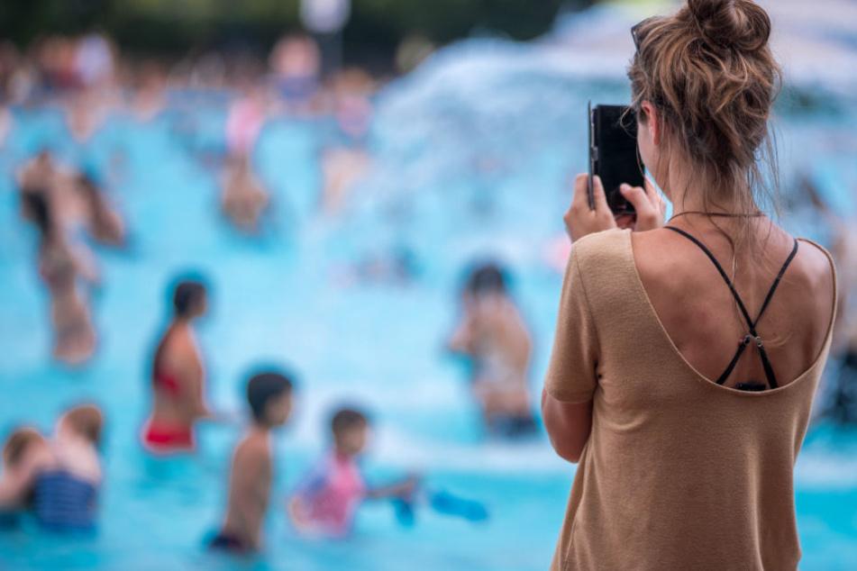 Eine junge Frau fotografiert mit ihrem Handy im Prinzenbad ihr schwimmenden Kinder.