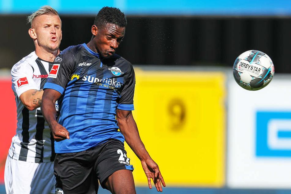 Paderborns Christopher Antwi-Adjej (r) kommt vor Freiburgs Jonathan Schmid an den Ball.