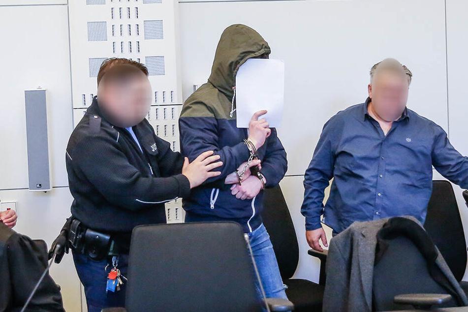 In Handschellen wurden die Angeklagten ins Gericht geführt.