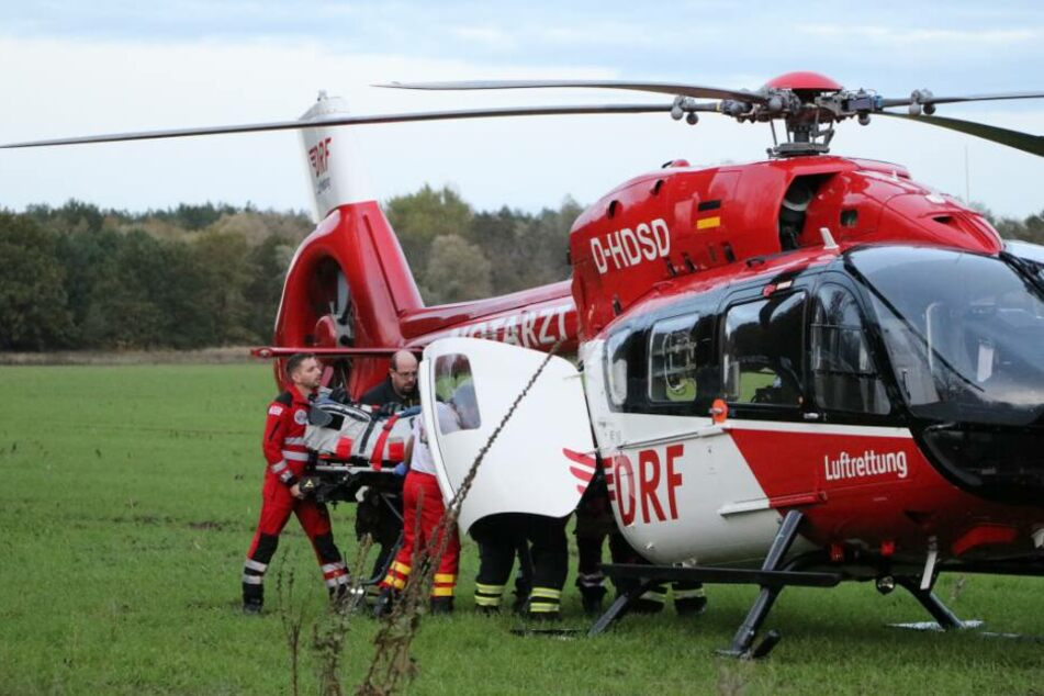 Rettungskräfte heben ein Unfallopfer auf einem Feld in einen Rettungshubschrauber. (Archivbild)