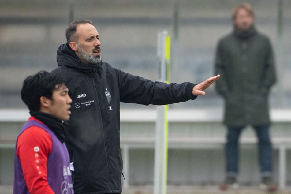 Pellegrino Matarazzo (M), Trainer des VfB Stuttgart, gestikuliert neben Wataru Endo (l). Im Hintergrund steht Sven Mislintat, Sportdirektor des VfB Stuttgart.