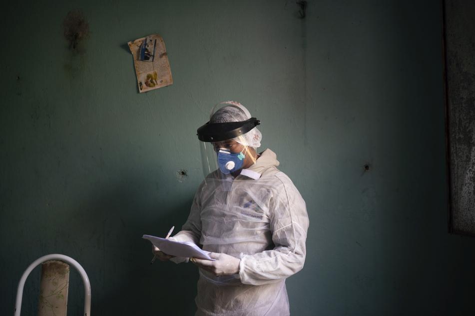 Der Mediziner Ari Nascimento macht sich Notizen, während er sich darauf vorbereitet, eine Probe für einen Corona-Test bei einer älteren Frau in Manacapuru zu sammeln.