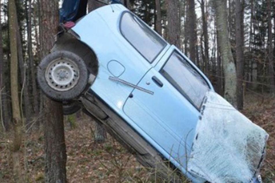 Der blaue Fiat hängt nach dem Unfall an einem Baum.