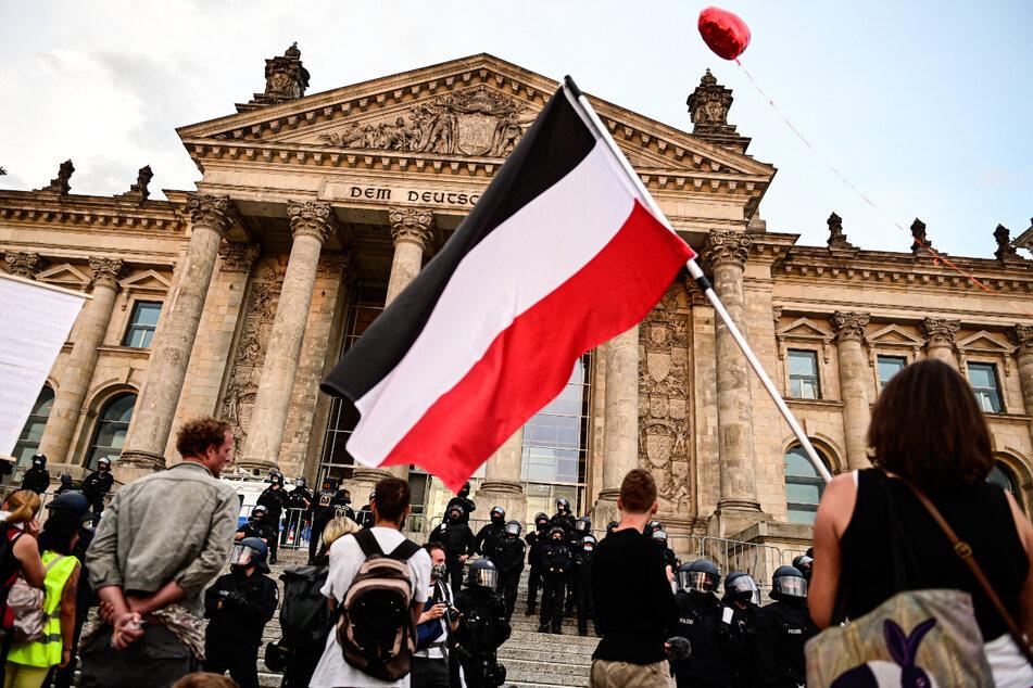 Berlin, 29. August 2020: Teilnehmer einer Kundgebung gegen die Corona-Maßnahmen stehen vor dem Reichstag, ein Teilnehmer hält eine Reichsflagge.