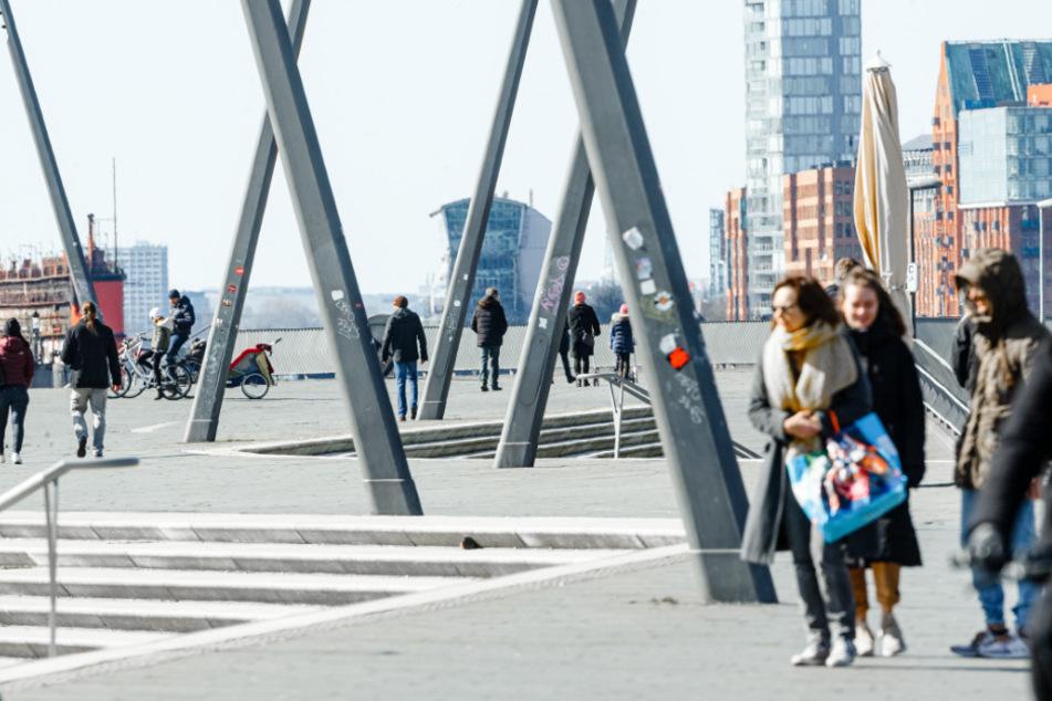 Nur wenige Fußgänger gehen am Hafen spazieren.