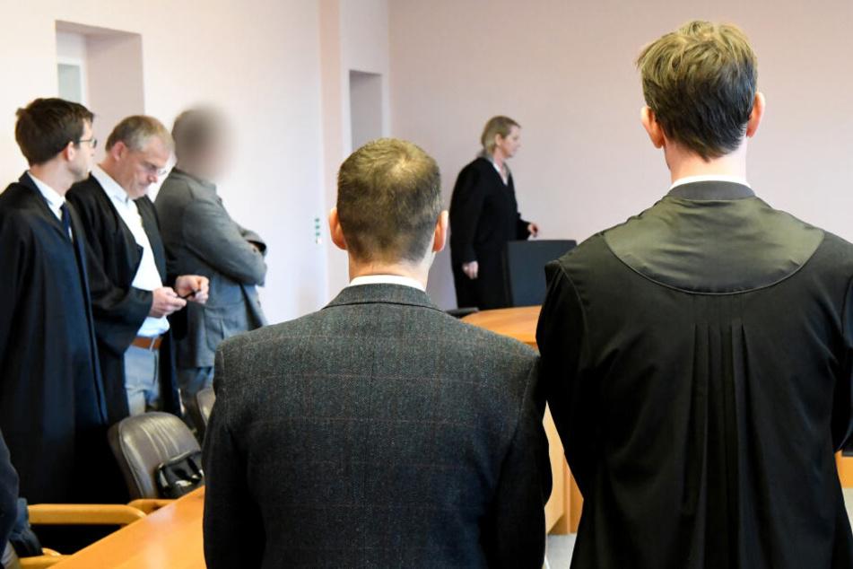 Zwei der Angeklagten (3.v.l und 4.v.l) stehen im Saal des Landgerichtes. In dem Prozess geht es um unrechtmäßige Pistolenlieferungen nach Kolumbien.