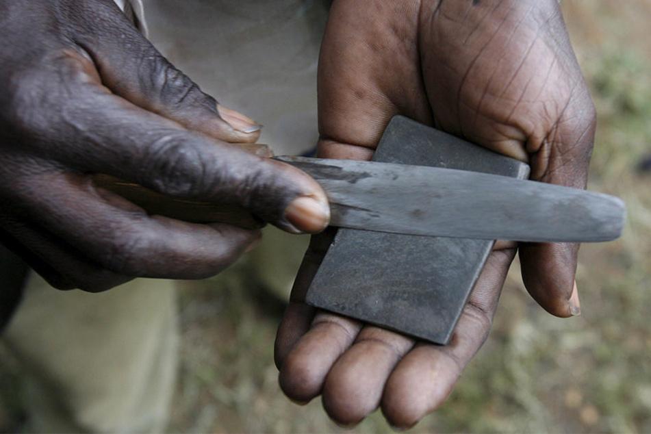 Ein Mann in Bungoma (Kenia) schärft sein Messer für die Beschneidung eines Jungen.