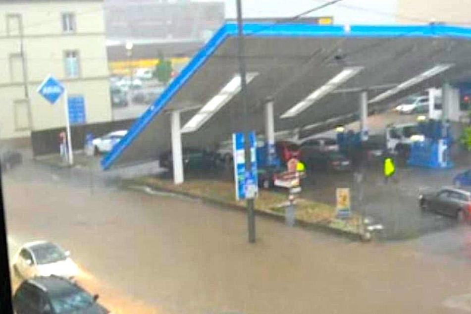 Hier wird eine Tankstelle vom Unwetter weggespült