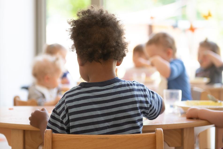 Die Kinder einer Kindergrippe sitzen im Rahmen der Notbetreuung während des Mittagessens an einem Tisch.