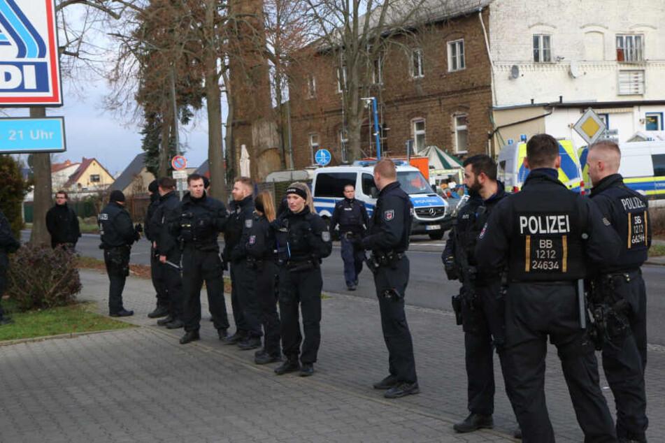 Ein Großaufgebot an Polizisten vor dem Parkplatz eines Supermarktes.