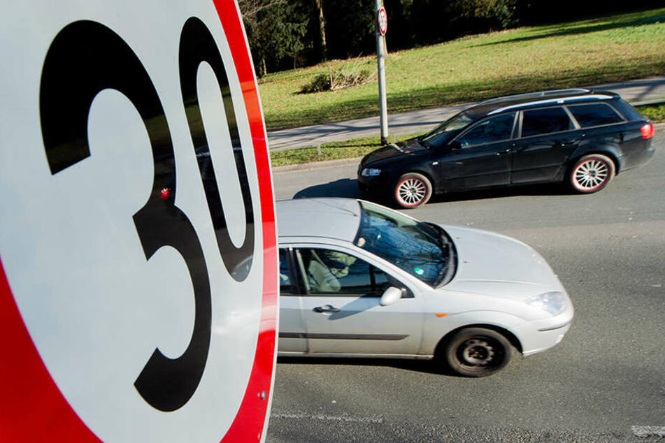 Autos fahren an einem Verkehrsschild für eine Geschwindigkeitsbegrenzung von 30 Stundenkilometer an Straße vor einer Schule vorbei.