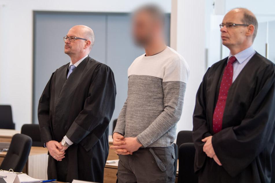 Der wegen Bildung einer terroristischen Vereinigung Angeklagte (M) wartet mit seinen Anwälten Michael Ohlendorf (l) und Patrick Graf zu Stolberg im Gerichtssaal auf den Beginn der Verhandlung.