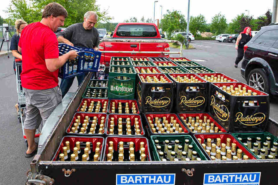 Bierkästen werden auf einen Anhänger geladen.