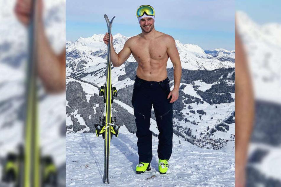 Alexander Hindersmann posiert mit freiem Oberkörper und Skiern in der Hand vor einer beachtlichen Bergkulisse.