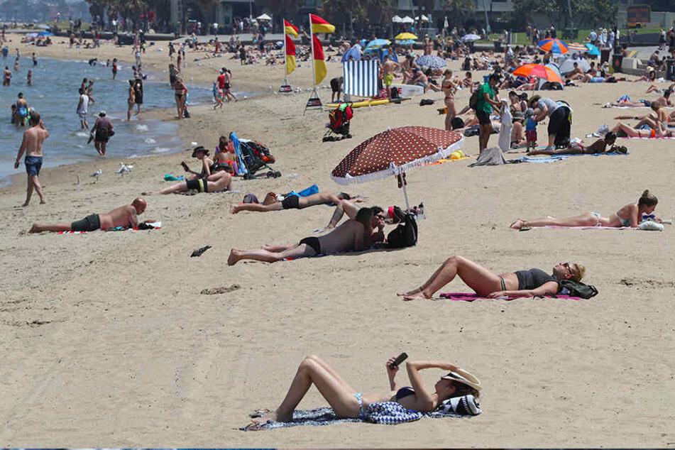 Strandbesucher liegen am Jahresende am Strand von St. Kilda in Melbourne.