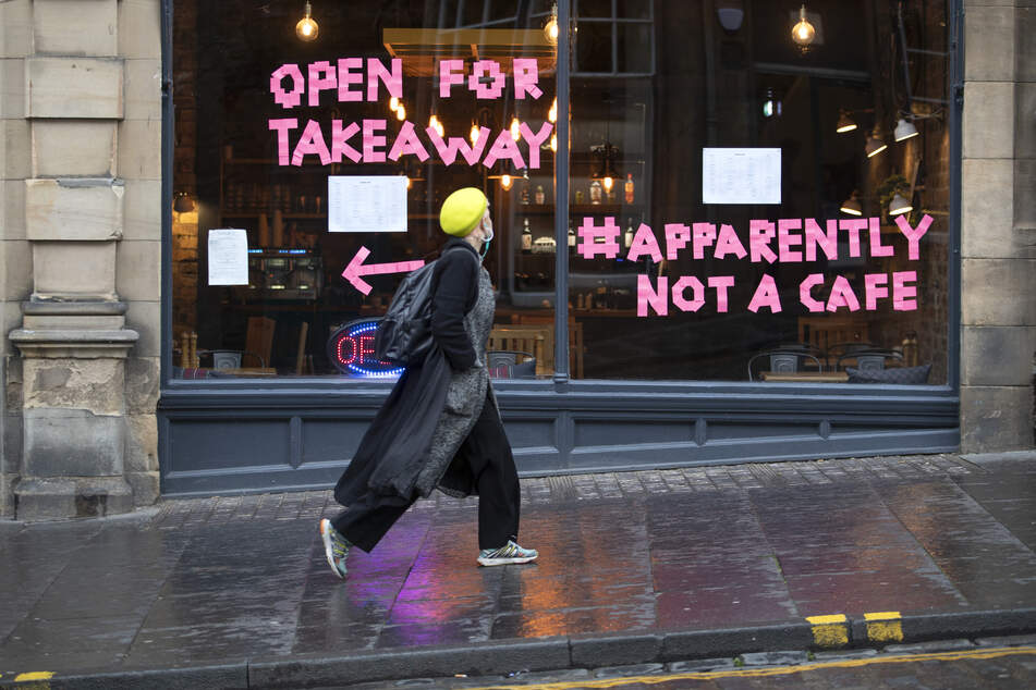 """Eine Frau geht auf der Cockburn Street am Bistro """"Scran"""" vorbei, auf dessen Fensterscheiben """"Open For Takeaway"""" (Für Essen zum Mitnehmen geöffnet) und der Hashtag """"Apparently Not a Cafe"""" (Anscheinend kein Café) steht."""