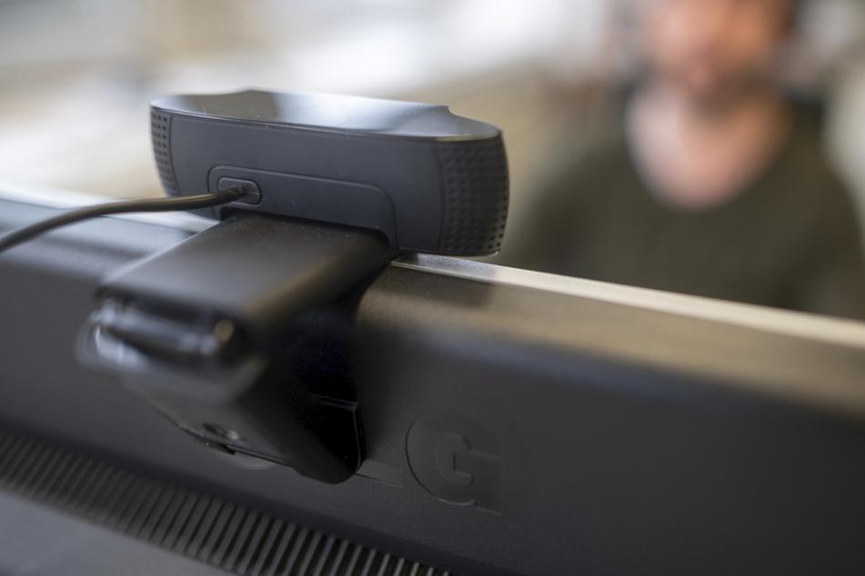 Ein junger Mann nimmt an einer Videokonferenz teil. Technische Tools sollen Studenten in Prüfungssituationen kontrollieren. (Symbolbild)