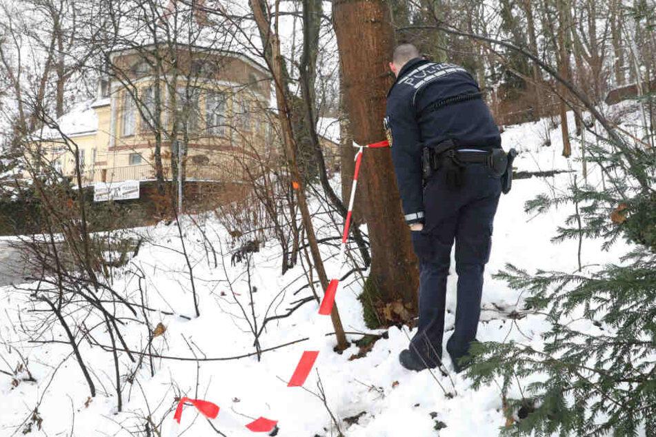 Ein Polizist entfernt Absperrband am Tatort im Bereich des Gigelbergs.