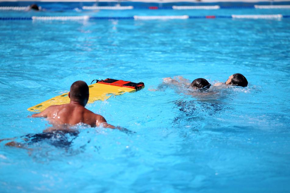Drei Rettungsschwimmer simulieren die Bergung einer bewusstlosen Person mit Hilfe eines neuen Spineboards.