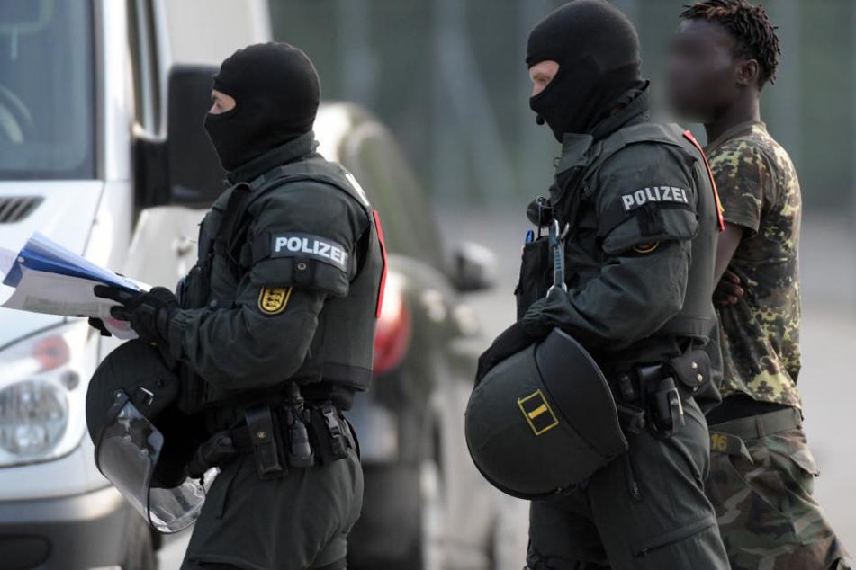 Maskierte Polizisten eskortieren einen Mann.