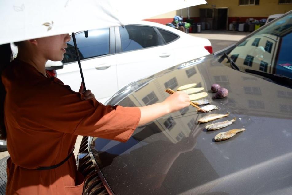 Das gibt's nur in China: Eine Frau brät bei Temperaturen um die 40 Grad Celsius Fisch und Süßkartoffeln auf der aufgeheizten Motorhaube eines Autos.