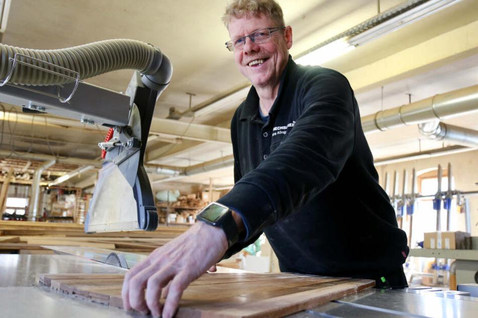 Drechslermeister Jens König legt in seiner Werkstatt ein Parkettmuster aus Merbau-Holz auf, wie es auch auf Schiffen der AIDA-Flotte verlegt wurde.