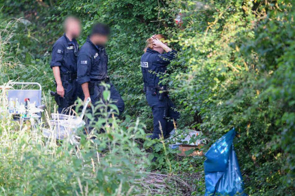 Polizisten untersuchen die Fundstelle der Leiche auf Spuren.