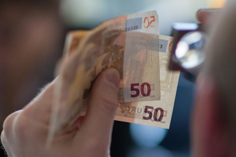 Ein Experte überprüft 50-Euro-Scheine auf ihre Echtheit.