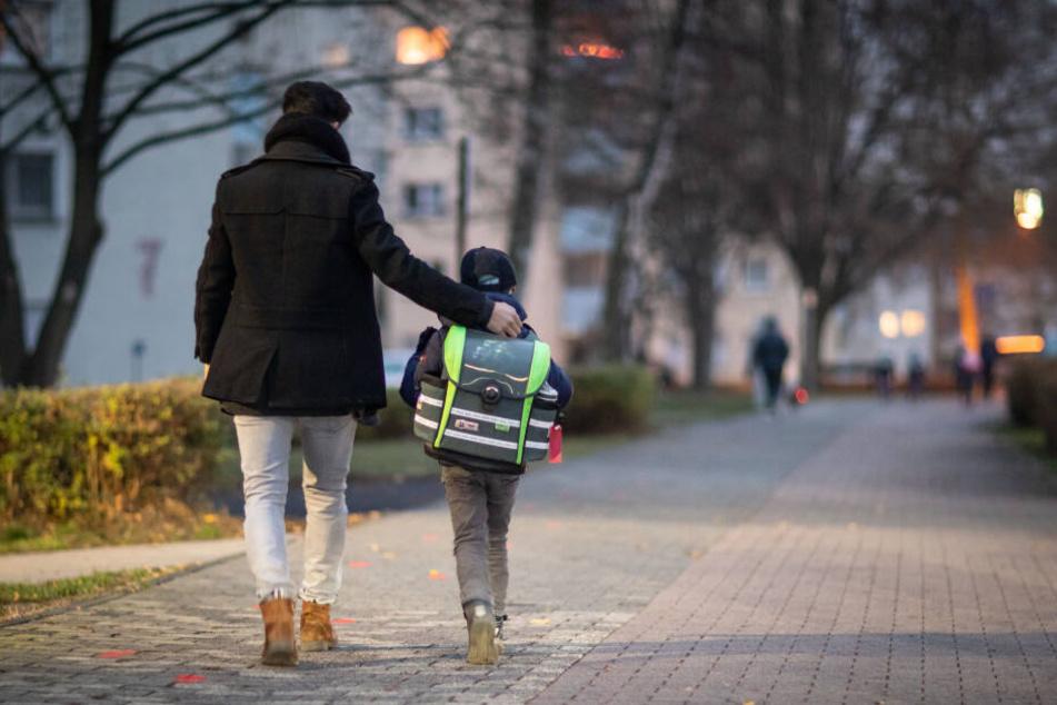 Ein Vater begleitet seinen Sohn auf dem Schulweg. Ein Schlafmediziner hat einen späteren Schulstart für sinnvoll. (Symbolbild)