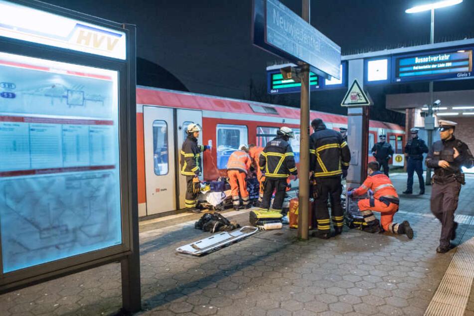 Rettungskräfte versorgen die verletzte Person am Bahnsteig.