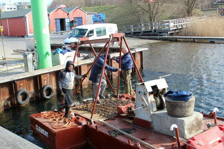 Mitarbeiter einer Rostocker Spezialfirma erweitern derzeit die Steganlage im Cospudener Hafen.