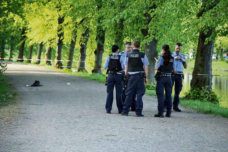 Mordversuch im Park: Polizisten haben den Tatort für die Spurensicherung abgesperrt. Die Tasche des Opfers liegt noch auf dem Asphalt.