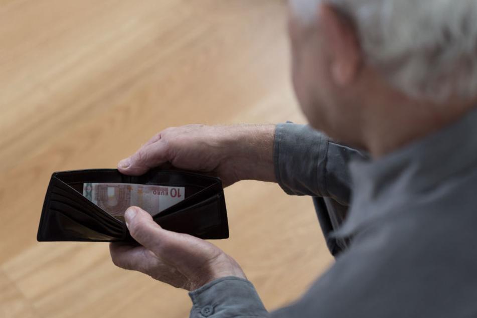 Ein Rentner blickt in sein Portmonee (Symbolbild).