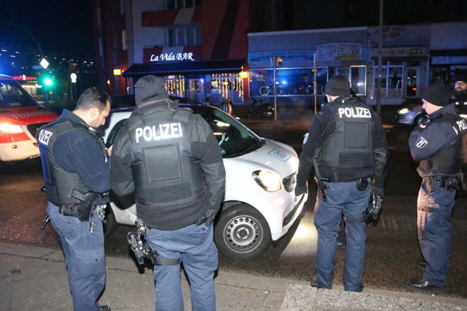 Polizisten stehen vor dem Carsharing-Smart.