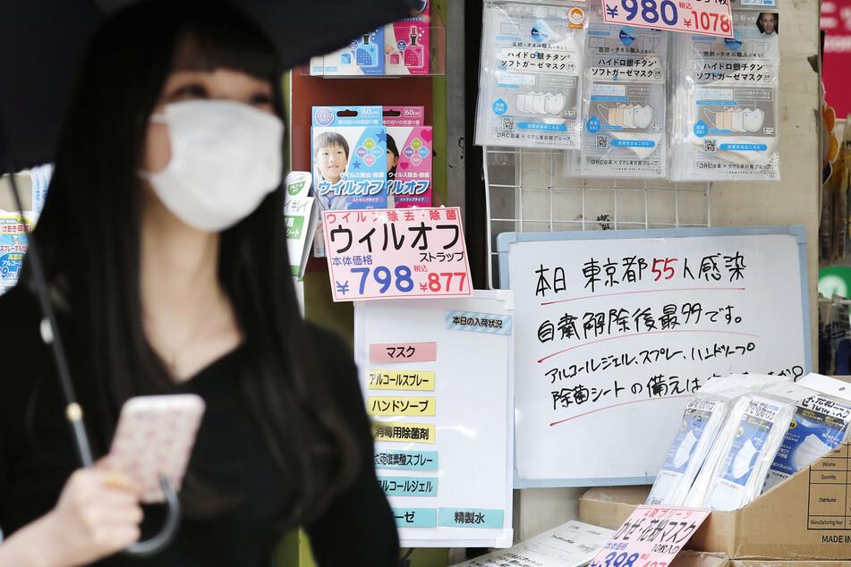 Eine junge Frau mit Mundschutz geht an einem Drogeriegeschäft vorbei, an dessen Eingang ein Zettel mit der Information über 55 neue Corona-Infektionen hängt.