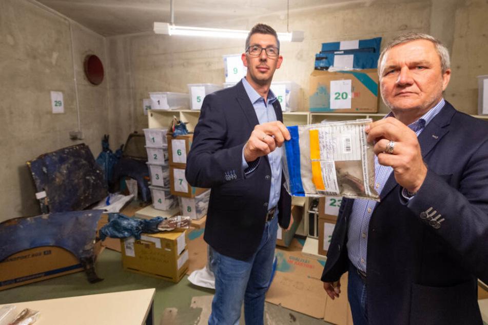Thilo Speich (links), stellvertretender Leiter der Ermittlungsgruppe Göhrde bei der Polizeidirektion Lüneburg, und Jürgen Schubbert, Leiter der Ermittlungsgruppe Göhrde, zeigen in der Asservatenkammer Teile eines Revolvers.
