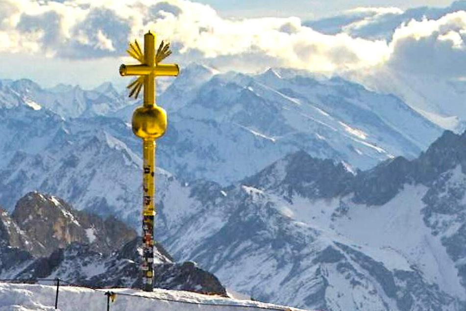 Das Foto aus einer Webcam zeigt das beschädigte Gipfelkreuz der Zugspitze, an dem rechts unten einige vergoldete Strahlen abgebrochen sind.