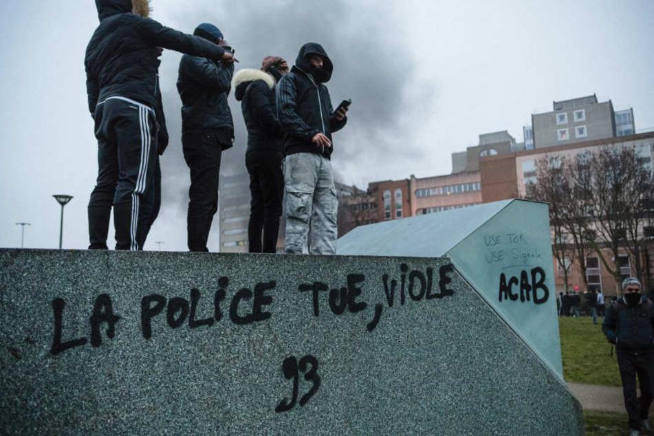 """Demonstranten stehen am Sonnabend in Bobigny bei Paris auf einem Container, um gegen Polizeigewalt zu demonstrieren. Auf dem Container steht """"Die Polizei tötet, vergewaltigt""""."""