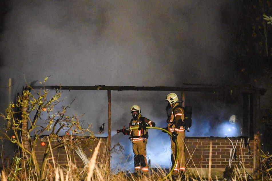 Feuerwehrmänner vor der völlig niedergebrannten Gartenlaube.