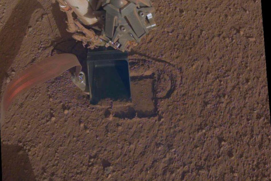 Dieses Foto zeigt den InSight Mars-Lander, der etwa einen Zentimeter unter der Oberfläche vom Mars gräbt.