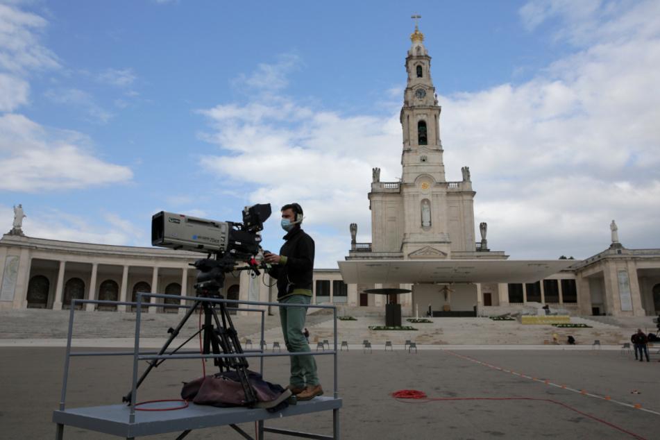 Portugal: Ein Kameramann richtet seine Kamera mit der Kathedrale von Fatima im Hintergrund vor dem Beginn der Feierlichkeiten am katholischen Wallfahrtsort ein.