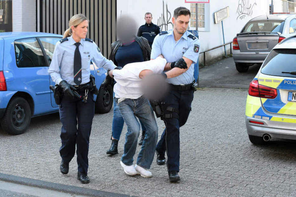 Essen am Freitag: Polizisten führen einen mutmaßlichen Verdächtigen ab. Im Hintergrund eine Zivilfahnderin der Polizei.