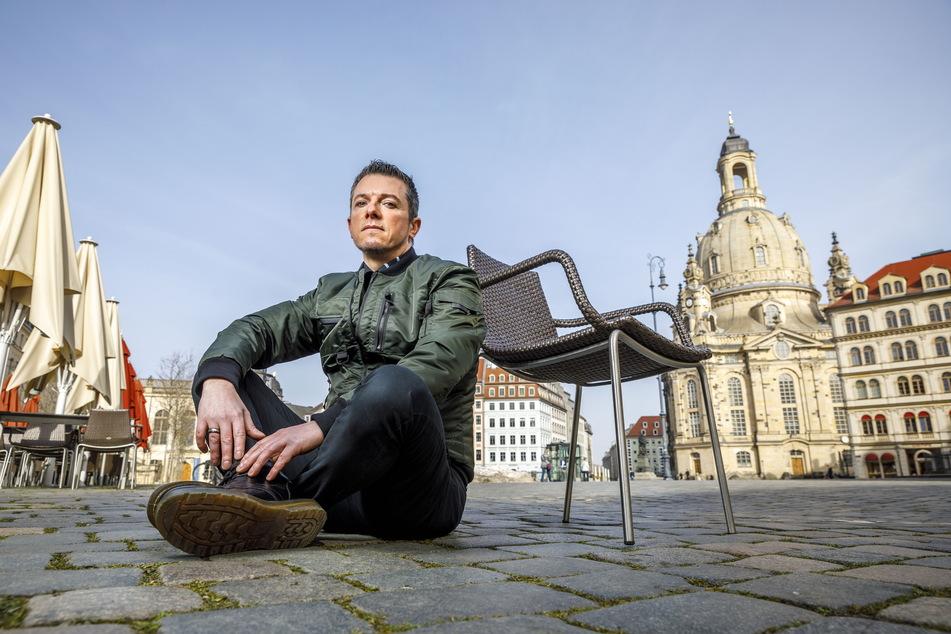 Noch sitzt Sänger Tom Reichel (47) ganz allein auf dem Dresdner Neumarkt.