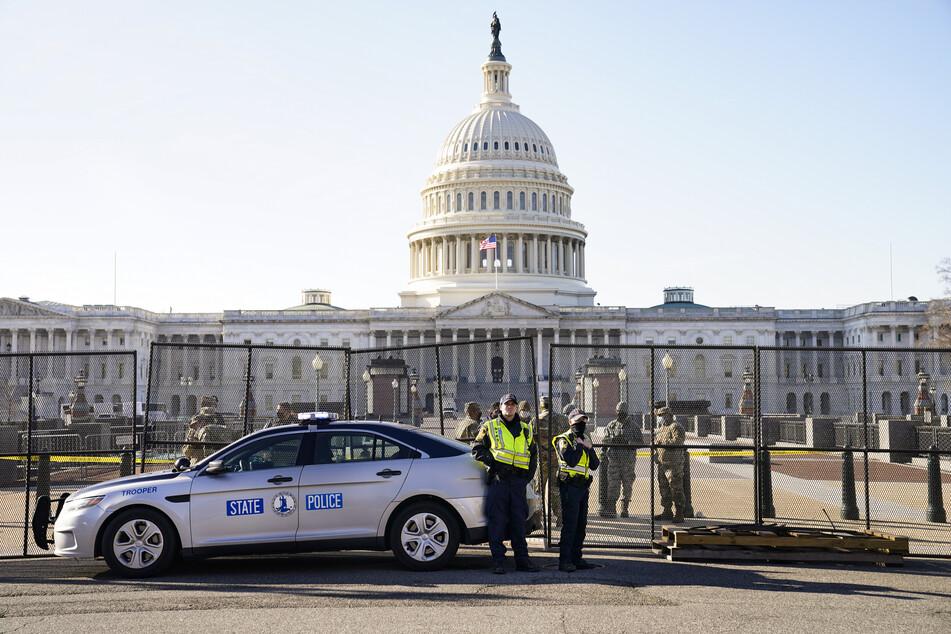 Soldaten und Polizeibeamte stehen vor dem US-Kapitol, während dort ein Sicherheitszaun errichtet wird.