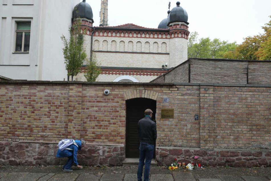 Menschen legen vor der Synagoge in Halle Blumen nieder.